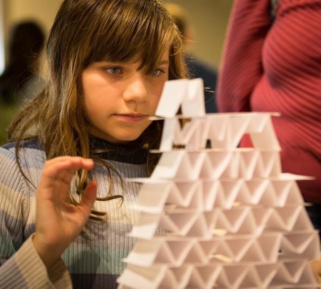 Young girl building a power tower
